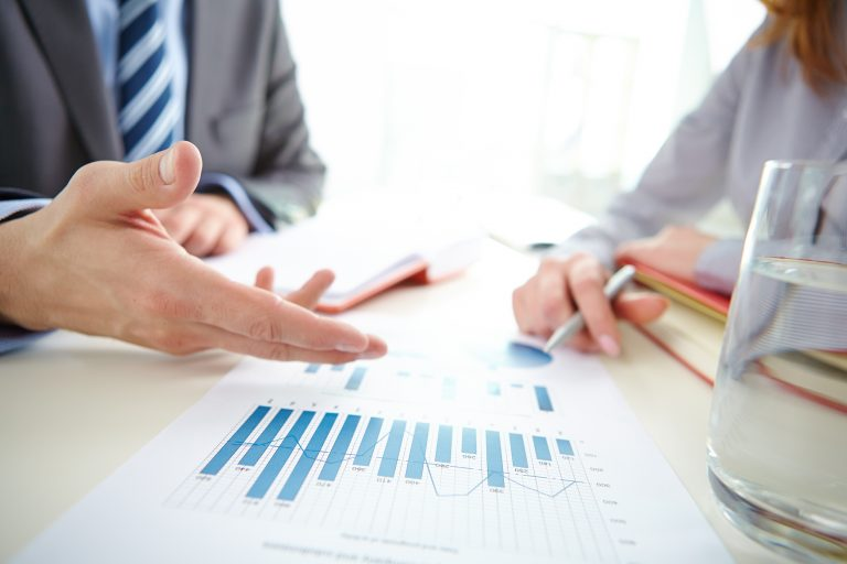 Businessman hand pointing at chart and graph during discussion